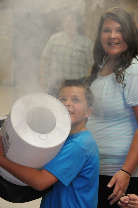 Photo by Bill Schaefer Ellis Elementary school second grade student Barrett Hobbs andhis mother Lynzi Hobbs watche the smoke expel from a bucket after hitting the bottom, one of many science demonstrations at the Haunted Science Lab.