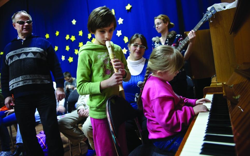 """PHOTO: BARTOSZ KRUPA/EAST NEWS OWINSKA, 29/01/2013. OSRODEK OPIEKUNCZO - WYCHOWAWCZY DLA DZIECI NIEWIDOMYCH W MIEJSCOWOSCI OWINSKA. N/Z: PROBA SZKOLNEGO CHORU """"DZIECI PAPY"""" POD PRZEWODNICTWEM NIEWIDOMEGO NAUCZYCIELA MUZYKI, PANA HENRYKA WEREDY. BASIA GRA NA FLECIE, DARIA NA PIANINIE. Owinska, Poland 29/01/2013 The school for blind children in Owinska. In the picture: """"Dzieci Papy"""" school choir rehearsal conducted by blind music teacher mr. Henryk Wereda. Basia is playing the flute and Daria is playing the piano."""