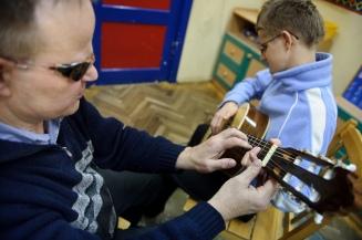 PHOTO: BARTOSZ KRUPA/EAST NEWS OWINSKA, 29/01/2013. OSRODEK OPIEKUNCZO - WYCHOWAWCZY DLA DZIECI NIEWIDOMYCH W MIEJSCOWOSCI OWINSKA. N/Z: PAN HENRYK UCZY DAWIDA GRY NA GITARZE. Owinska, Poland 29/01/2013 The school for blind children in Owinska. In the picture: Dawid is learning to play the guitar.