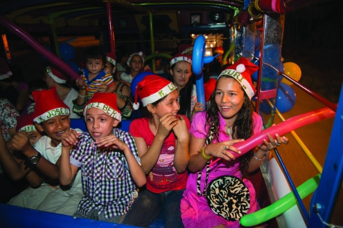 Puerta del Llano section of Kiwanis Club during a light tour with a vehicle called Chiva taking children to know Christmas lights installations in the streets an parks of Villavicencia, the capital city of Meta department, Southern Colombia.