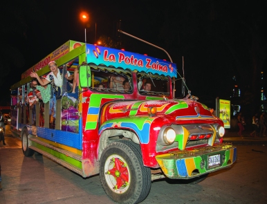 Canderia Ines Salazar Romero greats fron the front of the Chiva. Puerta del Llano section of Kiwanis Club during a light tour with a vehicle called Chiva taking children to know Christmas lights installations in the streets an parks of Villavicencia, the capital city of Meta department, Southern Colombia.