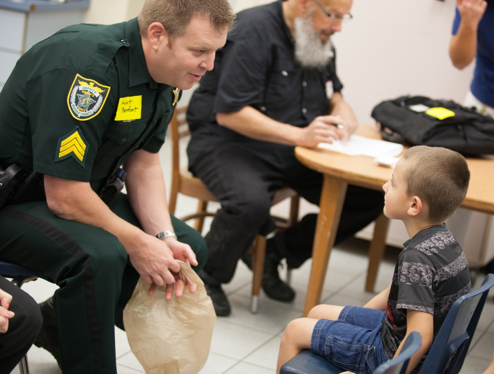 Fairglen Elementary School student Reilly Whidden tries on shoes with the help of Brevard County Sheriff's Office Kurt Benfont during the Kiwanis of Rockledge shoe distribution in Cocoa, Florida on Thursday, November 10, 2016.