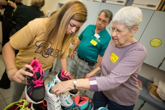 Rockledge High School Key Club member Bailey Campbell, left, receives shoes to try on a Fairglen Elementary School student during the Kiwanis of Rockledge shoe distribution in Cocoa, Florida on Thursday, November 10, 2016.