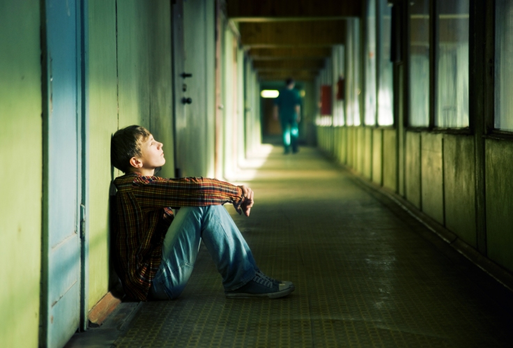Depressed teenager boy sitting on the corridor