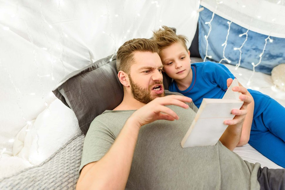 Emotional father and smiling son reading book while lying in bla