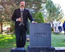 Scott Michlin, playing pioneer and merchant Frank M. Pierce, poses alongside Pierce's tombstone.
