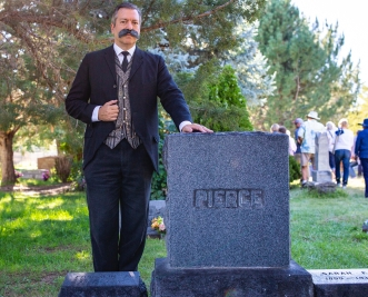 Scott Michlin, playing pioneer and merchant Frank M. Pierce, poses alongside Pierce's tombstone.