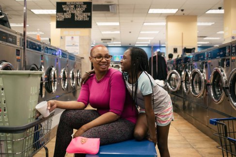 Berwyn, Illinois -- Wednesday, May 30, 2018 Thaisha Logan and her daughter Tashanna McKenzie, 9, spend time together at the World's Largest Laundromat. Logan, who lives across the street from the laundromat with her family, said that she wants her 9- and 3-year-old daughters to understand their surroundings. Reading is the essential to that lifeskill, she said, adding, ìI want my kids to understand everything thatís going on in this world.î The World's Largest Laundromat has created a literacy corner, a space designated for young people to play and read while their parents load laundry into the 300 washing and drying machines filling the facilityís 13,500 square feet. CREDIT: Alyssa Schukar for Kiwanis Magazine