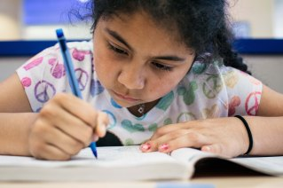 Berwyn, Illinois -- Wednesday, May 30, 2018 Jasmine Perez, 9, works on her English practice book as her family does the week's laundry. The World's Largest Laundromat has created a literacy corner, a space designated for young people to play and read while their parents load laundry into the 300 washing and drying machines filling the facilityís 13,500 square feet. CREDIT: Alyssa Schukar for Kiwanis Magazine