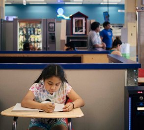 Berwyn, Illinois -- Wednesday, May 30, 2018 Jasmine Perez, 9, works on her English practice book as her family does the week's laundry. The World's Largest Laundromat has created a literacy corner, a space designated for young people to play and read while their parents load laundry into the 300 washing and drying machines filling the facility's 13,500 square feet. CREDIT: Alyssa Schukar for Kiwanis Magazine