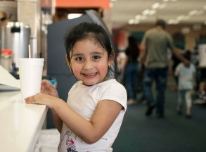 Berwyn, Illinois -- Wednesday, May 30, 2018 Arlin Torres, 4, waits for a slice of pizza as her family does the week's laundry. The World's Largest Laundromat has created a literacy corner, a space designated for young people to play and read while their parents load laundry into the 300 washing and drying machines filling the facility's 13,500 square feet. CREDIT: Alyssa Schukar for Kiwanis Magazine