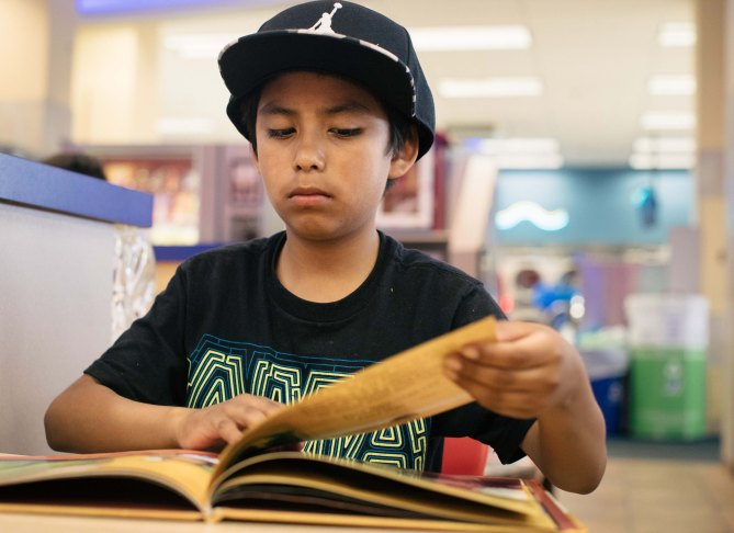 """Berwyn, Illinois -- Wednesday, May 30, 2018 Isaac Cervantes, 11, reads the Spanish language book """"Un Neal de Buranas Noches"""" at the World's Largest Laundromat. The World's Largest Laundromat has created a literacy corner, a space designated for young people to play and read while their parents load laundry into the 300 washing and drying machines filling the facilityís 13,500 square feet. CREDIT: Alyssa Schukar for Kiwanis Magazine"""