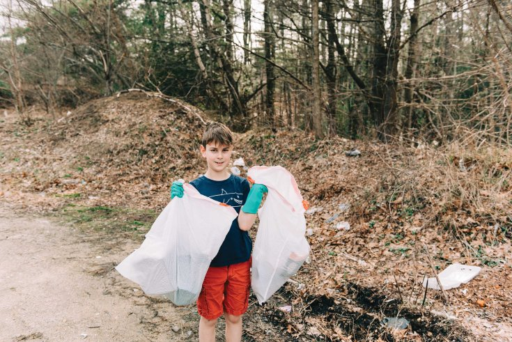 stock photo of little boy posing with trash bags that he picked up on earth day